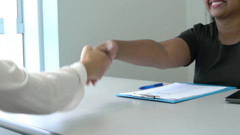 Two businesswoman of different ethnicity shake hands Live Action