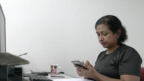 Asian Indian businesswoman texting or messaging on her cellphone at her workstation. Office setting Live Action