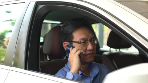Asian businessman talking on the cellphone inside his car with windows open Live Action