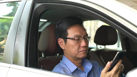 Businessman viewing or reading messages on his cellphone inside his car Live Action