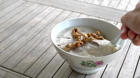 Rice porridge with pork meat in a bowl. Closeup. Asian cuisine Live Action