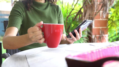 Woman drinking her coffee in red cup while surfing on her cellphone Live Action