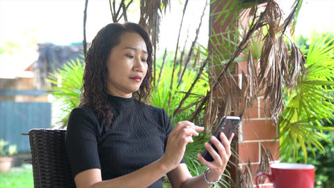 Asian chinese businesswoman surfing her cellphone Live Action