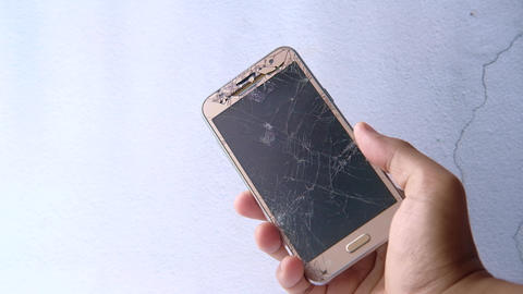 Close up of hand holding broken smart phone Live Action