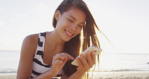 Woman sms texting using phone app on smartphone at beach sunset ライブ動画