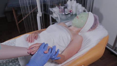 Professional beautician does hand massage to woman Live Action