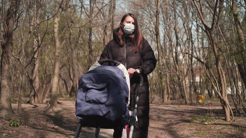 Mom in a protective mask with a pram is walking in the park among the trees Live Action