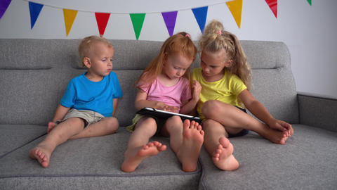 Three Little Children Playing With Tablet Computer PC. Redhead girl playing Live Action