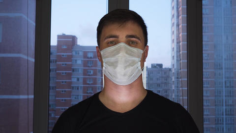 A man in a medical protective mask stands at home against the background of the Live Action