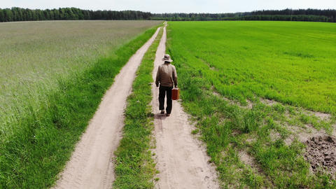 man alone walking by country road in a green field, holding suitcase in a hand Live Action