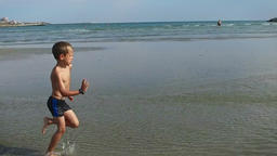 Little boy running on a beach, slow motion Footage