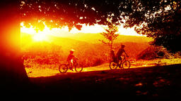 Father and sons on bicycles, mountain range sunset Footage