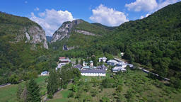 Aerial view of Polovragi Monastery surrounded by forest, Romania, landing Footage