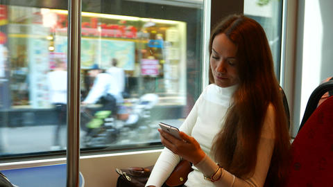 Thoughtful woman stare to smartphone, travel in tram at shopping street Footage