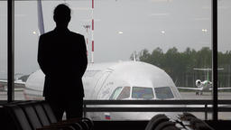 Man silhouette stand against terminal window, big airliner parked outside Footage
