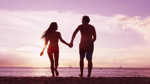 Happy couple cheering on beach enjoying sunset on summer travel vacation holiday Live Action