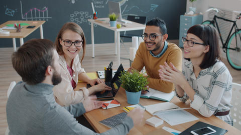 Joyful colleagues talking at desk in office then doing high-five and laughing Live Action