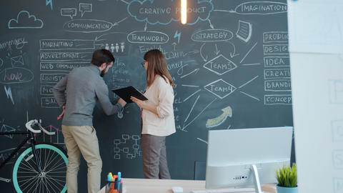 Businesswoman talking to male colleague who is writing information on chalkboard Live Action