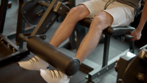 Unknown bodybuilder making leg extension in sport club. Legs training at gym Live Action