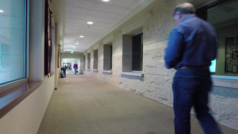 Cancer hospital long hall patient walking away HD 892 Footage