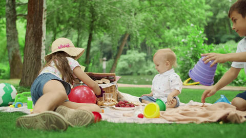 Cheerful siblings having picnic in park together. Cute children resting outside Live Action