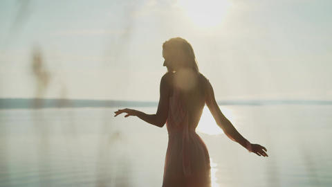 carefree woman dancing in the sunset on the beach. vacation vitality healthy Live Action