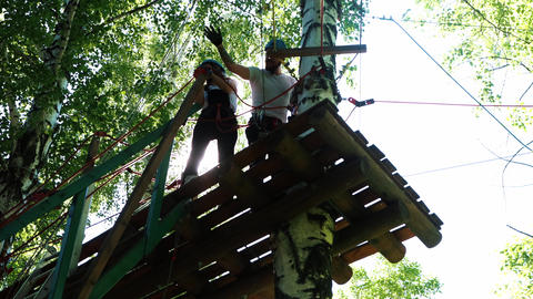 Rope adventure - woman and man standing on the suspension bridge and waving Live Action