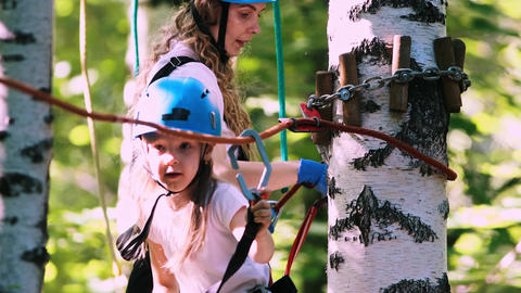 Extreme rope adventure in the park - young family of little girl and her mother Live Action
