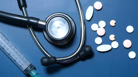 pills, stethoscope and syringe on blue background Live Action