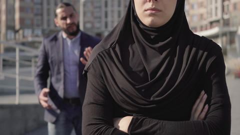 Unrecognizable muslim woman in traditional clothes standing with hands crossed Live Action
