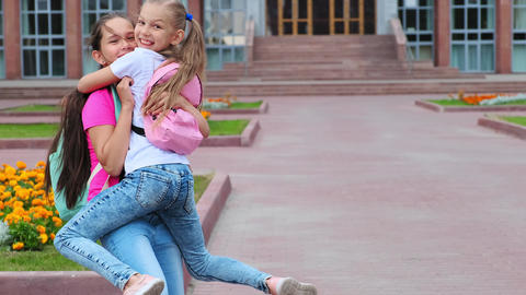 girl holds happy friend having fun near school building Live Action