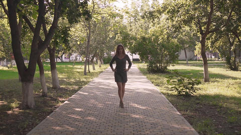 Cute girl in the park among the trees. A happy girl in a gray dress is dancing Live Action