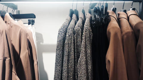 Stylish clothes in boutique store, modern shop interior, luxury shopping and Live Action