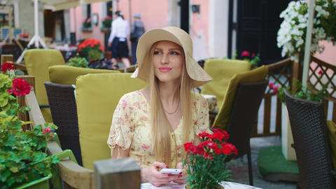 Smiling girl in outside restaurant. Cheerful young woman sitting at table in Live Action
