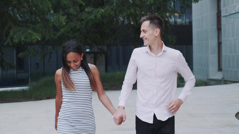Two mixed-race sweethearts having fun running together in park Live Action