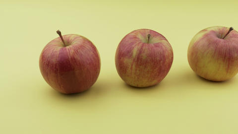 Organic red apples on a yellow background Live Action
