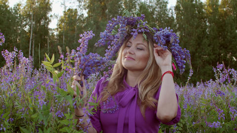 Attractive young woman in floral wreath on blooming meadow Live Action