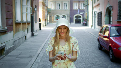 Woman texting on street. Cheerful young lady in white hat walking on old town Live Action