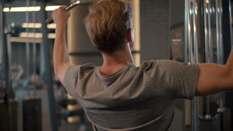 Active bodybuilder man training at gym. Fit man making pulldown in sport club Live Action