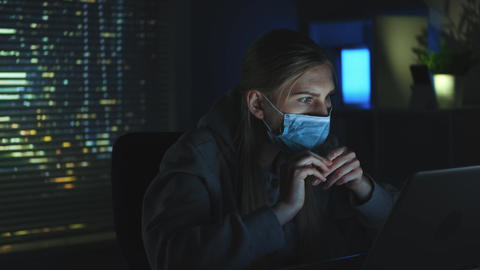 Close-up shot of Scared woman in medical mask reading news about coronavirus on Live Action
