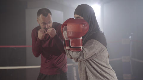 Positive muslim woman standing in boxing stance as Caucasian man talking at the Live Action