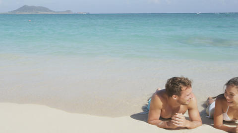 Honeymoon beach couple sun tanning relaxing on holiday travel Live Action