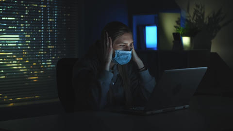 Scared woman in medical mask reading news about coronavirus on laptop in Live Action