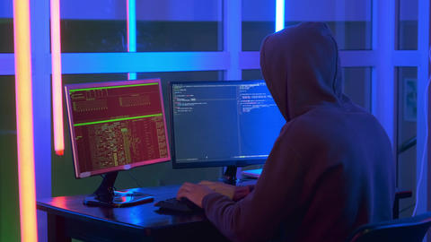 Medium shot of hacker dressed in a dark close working on computer Live Action