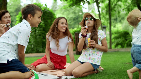 Boys and girl playing in forest. Laughing parents relaxing with children in park Live Action