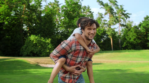 Father spinning around in park with son on back. Funny family having fun outside Live Action