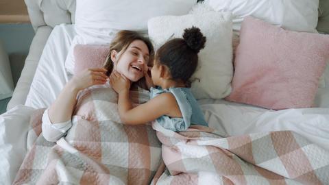 Portrait of mommy and black girl lying under blanket hugging kissing playful Live Action