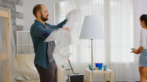 Man wrapping lamp with plastic poil Live Action