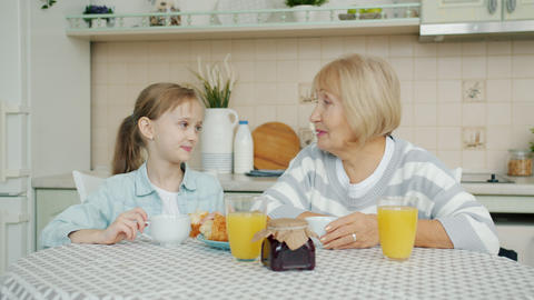 Joyful family granddaughter and grandmother having breakfast at home talking Live Action