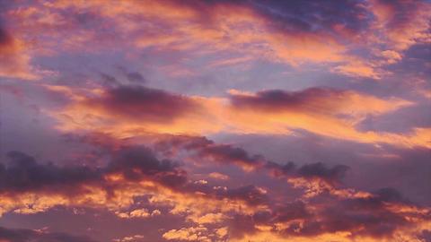 Clouds colored by the setting sun move through the evening sky Acción en vivo